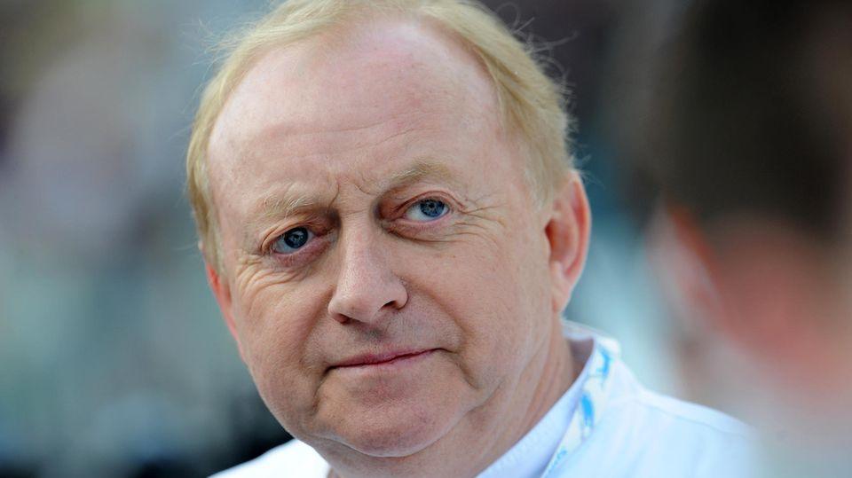Ein weißer Mann mit rundlichem Gesicht und dünnem, blonden Seitenscheitel trägt eine weiße Kochjacke und schaut skeptisch