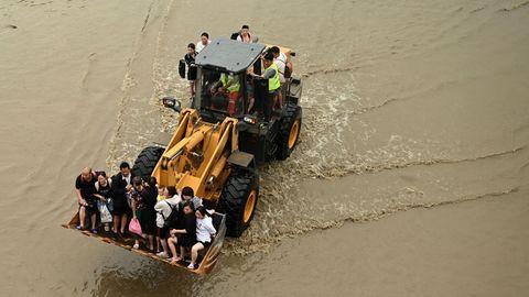 Ein gelber Radlader fährt mit einer Schaufel voller stehender Menschen und auf dem Heck stehenden Menschen durch braunes Wasser