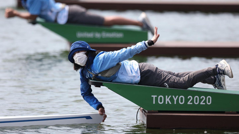 Tokio, Japan. Diese Helferin soll bei den Olympia-Vorläufen im Sea Forest Waterway ein Ruderboot in Startposition halten – und hat dabei sichtlich Mühe, Haltung zu wahren.
