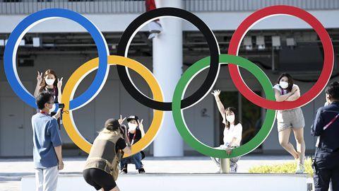 Menschen posieren vor den Ringen der Olympischen Spiele.