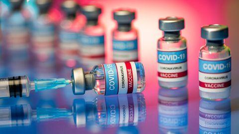 Ampullen mit Corona-Impfstoff stehen aufgereiht, der Inhalt einer Ampulle wird in eine Spritze gezogen
