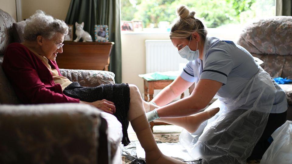 Corona Impfung: Eine Pflegerin kümmert sich um eine ältere Frau