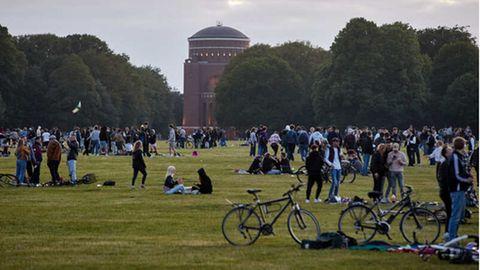 Jugendliche sitzen auf der Festwiese des Hamburger Stadtparks