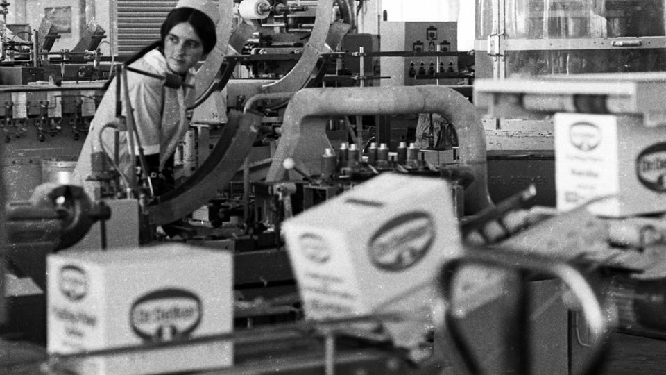 Ein Schwarzweiß-Foto zeigt eine junge Frau an einer Produktionsstraße von Lebensmitteln