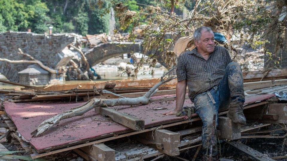 Ein Helfer ruht sich auf Treibgut und Trümmern aus