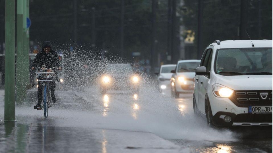 Eine Radfahrerin wird vom Spritzwasser eines Autos getroffen