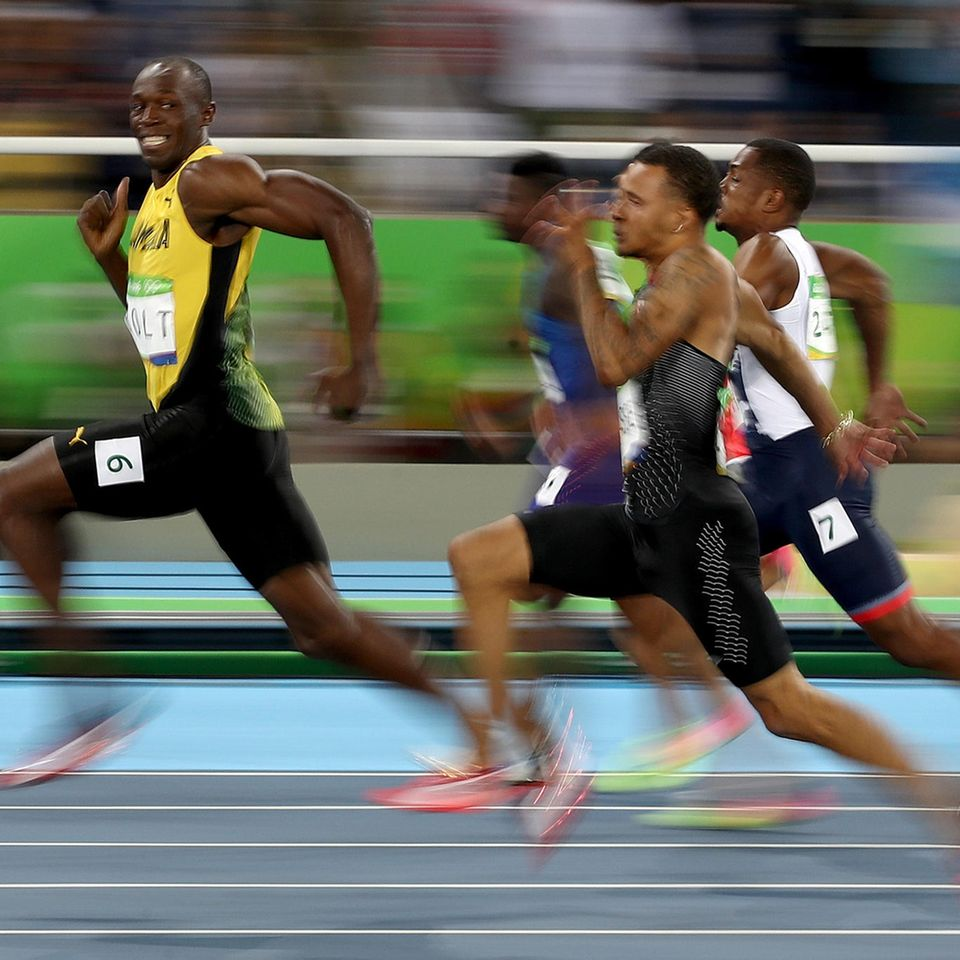 """Wohl eins der ikonischsten Bilder der Olympischen Sommerspiele 2016: Der Fotograf Cameron Spencer hält Usain Bolt dabei fest, wie er seinen Konkurrenten im Halbfinale des 100-Meter-Laufs der Männer davonläuft. Bolt gewann in diesem Jahr bei den Olympischen Spielen in Rio sein """"Triple Triple"""", indem er die 100 Meter, 200 Meter und den 4x100 Meter-Lauf gewann, so wie er es bereits bei den Spielen in London 2012 und Peking 2008 getan hatte."""