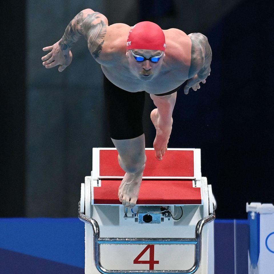 Tokio, Japan:Der Fotograf Jonathan Nackstrand hat den Moment festgehalten, in dem der britische Schwimmer Adam Peaty gerade den Startblock verlässt. Gleich taucht er in das kühle Wasser ein und kämpft im Vorlauf der100 Meter Brust der Männer um den Einzug ins Halbfinale. Mit Erfolg: Peaty erreichte als Erster das Ziel und darf morgen erneut ins Becken springen.