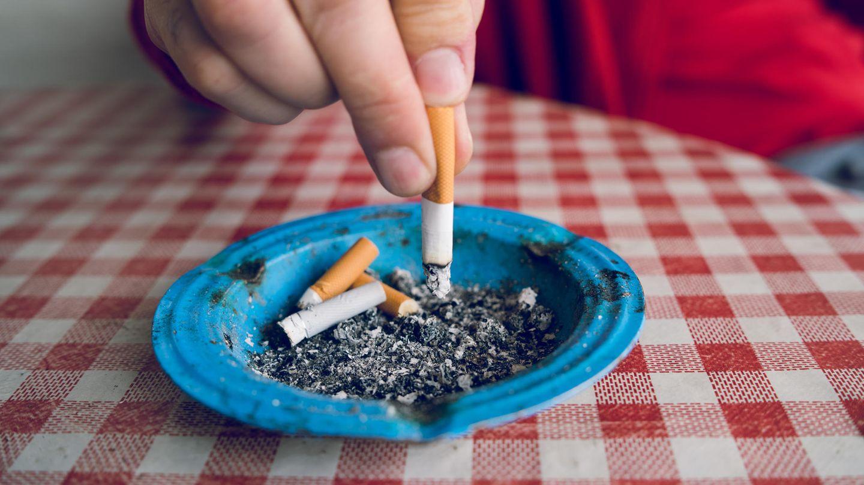 Eine Hand drückt eine Zigarette in einem Aschenbecher aus