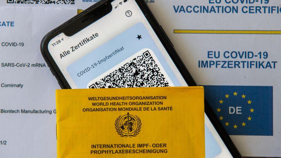 Ein Impfpass und ein Smartphone, auf dem die App CovPass läuft, liegen auf einem Impfzertifikat