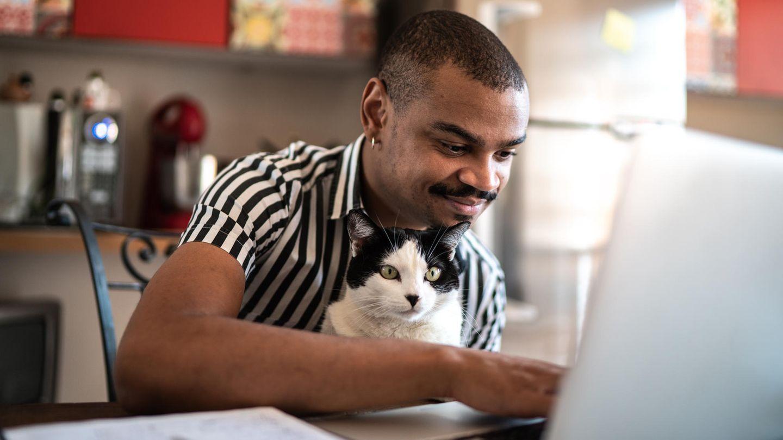 Ein Mann mit einer Katze auf dem Schoß