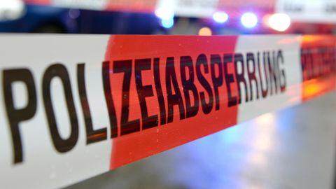 """Ein Flatterband mit der Aufschrift """"Polizeiabsperrung"""" hängt an einem Einsatzort"""