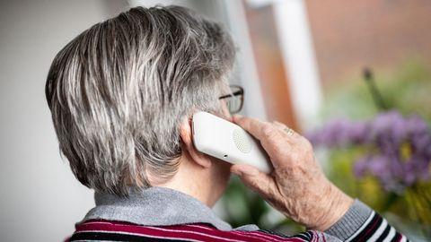 Seniorin telefoniert und schaut dabei aus dem Fenster.