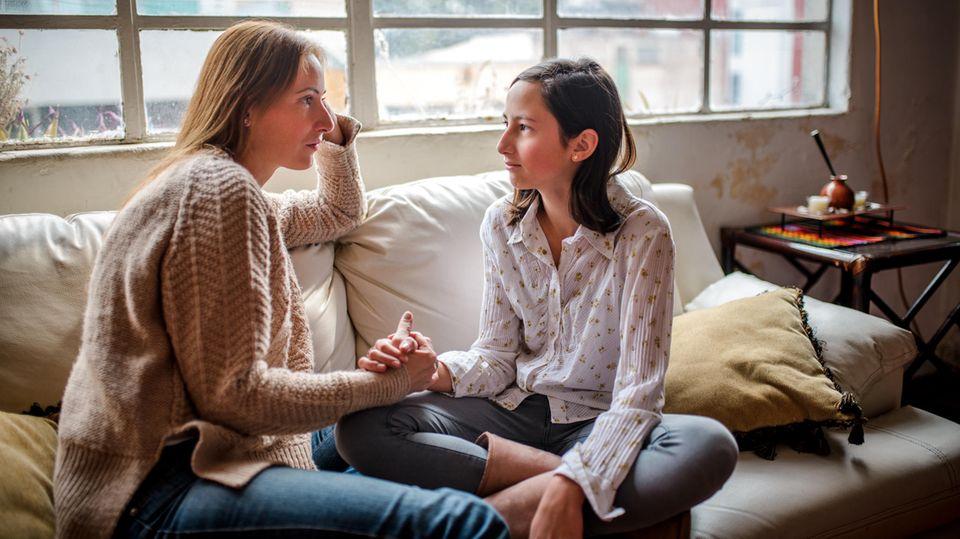 Mutter und Tochter sitzen gemeinsam auf dem Sofa und führen ein ernstes Gespräch
