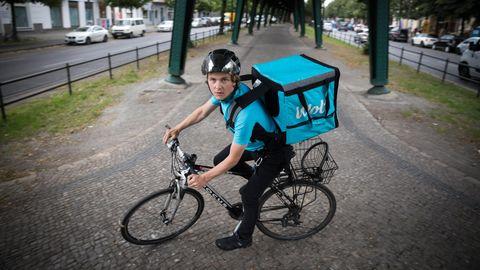 Ein Lieferant auf dem Fahrrad blickt in die Kamera