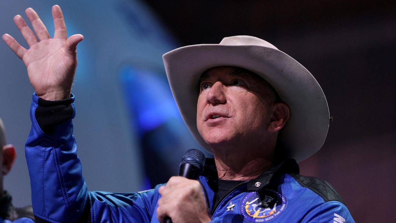 Jeff Bezos im Raumanzug und mit Cowboyhut hebt seine Hand in den Himmel