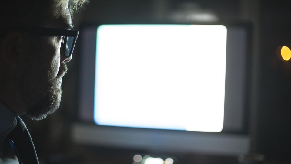 Mann in einem dunklen Raum vor Monitor