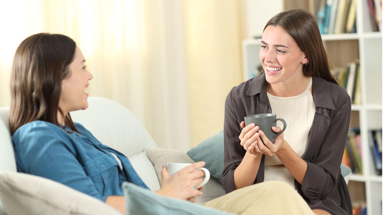 Zwei junge Frauen sitzen mit Tassen in der Hand auf dem Sofa und unterhalten sich glücklich.