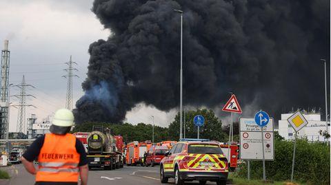 Einsatzfahrzeuge der Feuerwehr stehen unweit einer Zufahrt zum Chempark Leverkusen