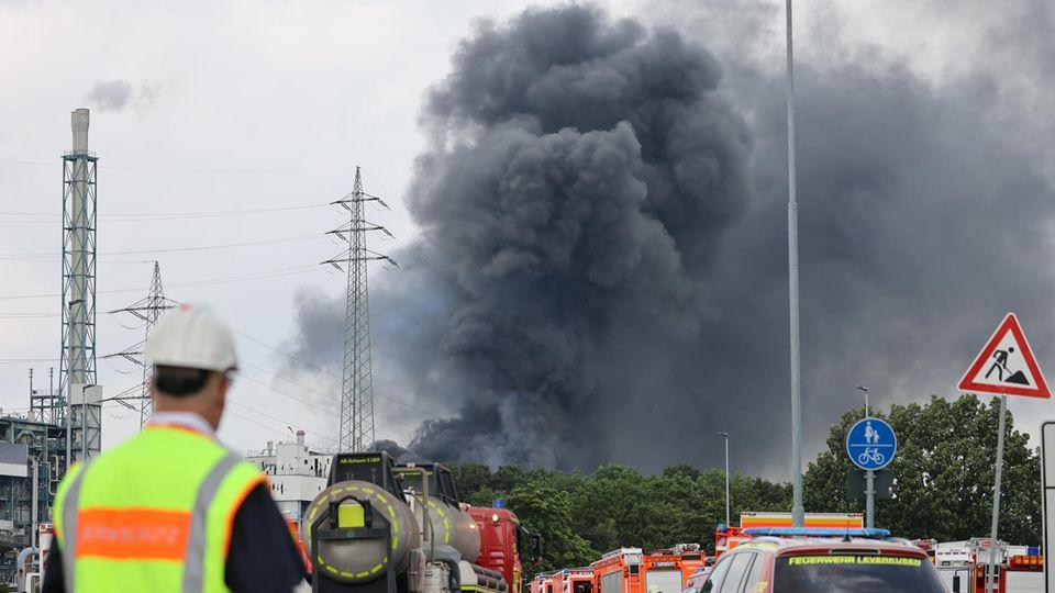Einsatzfahrzeuge der Feuerwehr stehen unweit einer Zufahrt zum Chempark über dem eine dunkle Rauchwolke aufsteigt