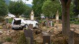 Bad Neuenahr-Ahrweiler, Deutschland. Es wirkt wie ein Fanal. Ein Auto, das von der Flut mitgerissen wurde, ist auf einem Grabfeld gelandet. Auch der Friedhof der Stadt wurde bei der Katastrophe völlig verwüstet. Im Landkreis Ahrweiler kamen durch die Flut 132 Menschen ums Leben, immer noch werden 73 Personen vermisst.