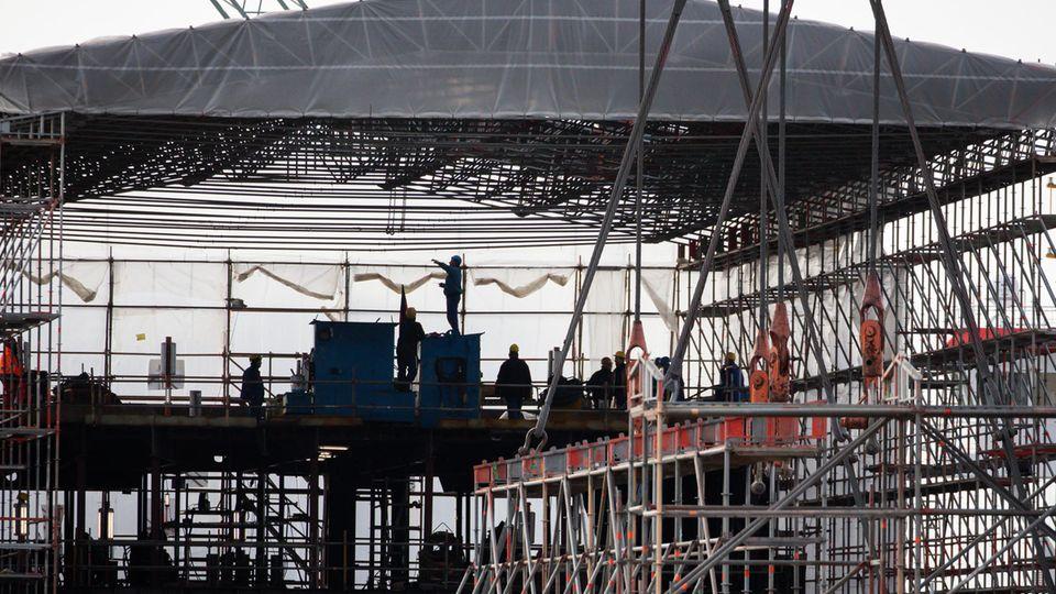 Werftarbeiter arbeiten in einer Halle auf dem Gelände der Pella Sietas Werft