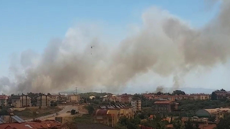 Dunkler Rauch steigt über einem Wohngebiet in den Himmel auf