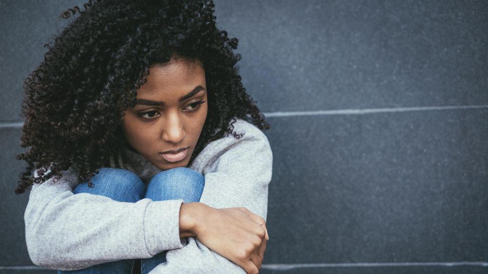 Eine junge schwarze Frau hockt an einer Wand auf dem Boden und sieht traurig aus