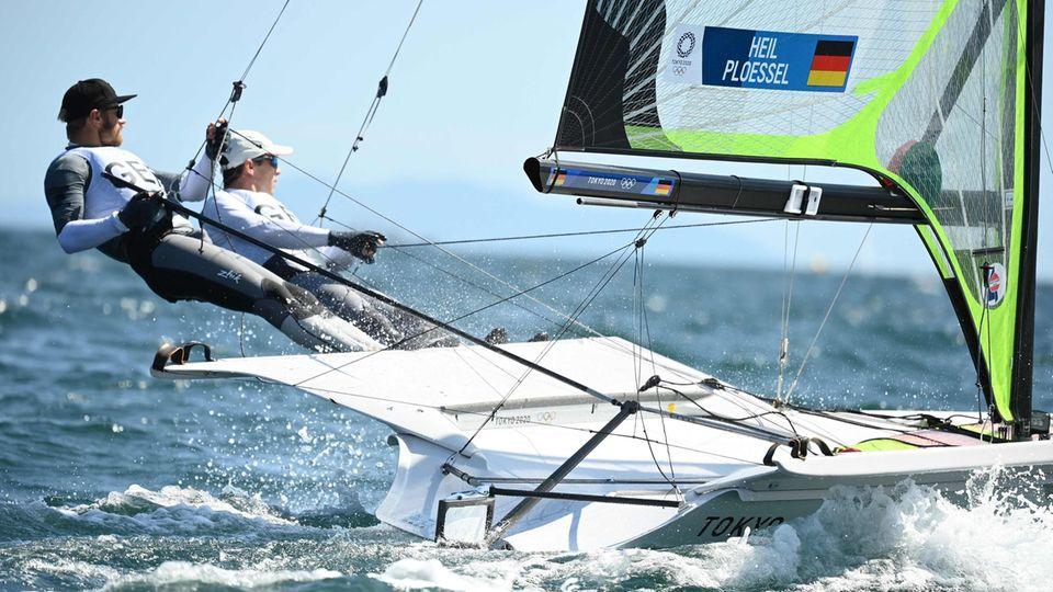 Zwei Segler stehen auf der Kante eines schnellen Segellbootes, während sie an Drahtseilen gesichert sind
