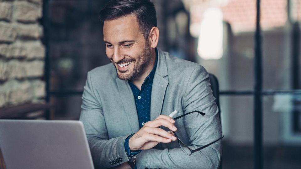 Ein Mann sitzt lächelnd vor seinem Business-Laptop.