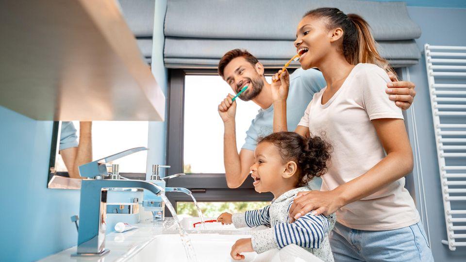 Zahnpflege: Mann, Frau und Mädchen putzen sich vor dem Spiegel die Zähne