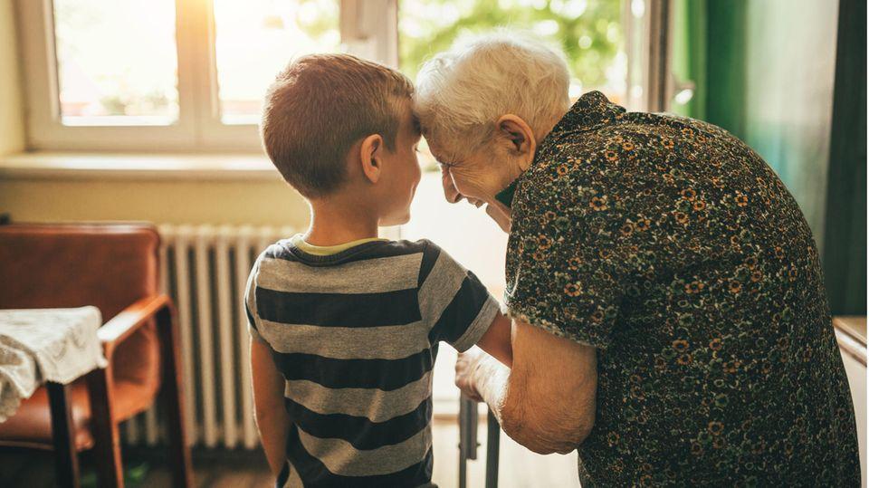 Ältere Dame und kleiner Junge lächeln sich an