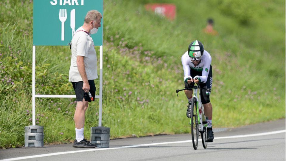 Ein Mann steht am Streckenrand, während ein Rennradfahrer in Montur an ihm vorbeifährt