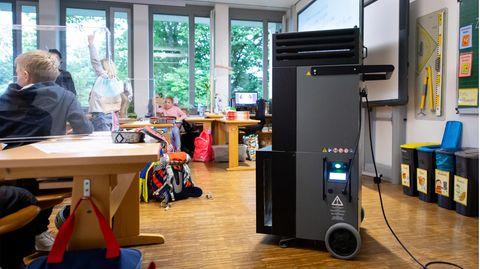 Ein schwarz-grauer Quader auf Rollen und mit Luftschlitzen im oberen Bereich steht in einem Klassenzimmer mit Grundschülern