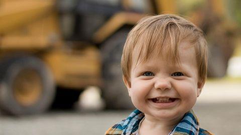 Ein kleiner Junge steht vor einem Bagger und grinst