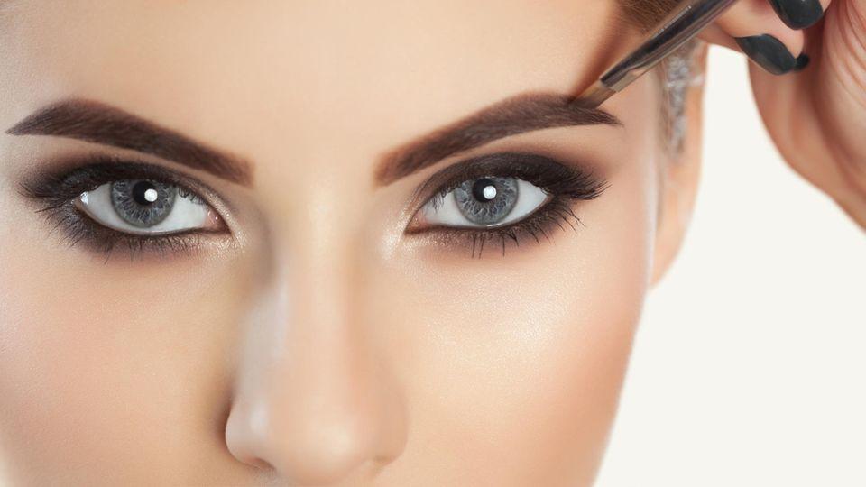 Eine Frau malt ihre Augenbrauen an