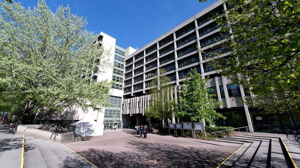 Ein mehrstöckiger Betonbau steht hinter einem quadratischen, asphaltiertem Platz, der von einigen Laubbäumen umgeben ist