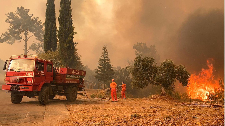 Ein Löschfahrzeug und zwei Feuerwehrleute in einer brennenden Landschaft
