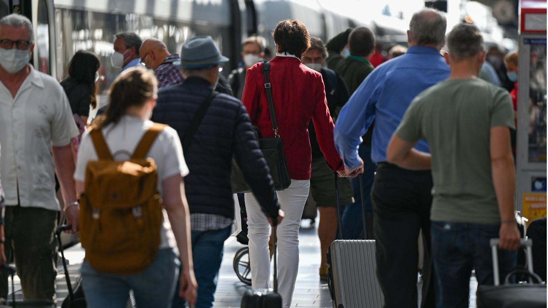 Viele Reisende laufen durch einen Bahnhof