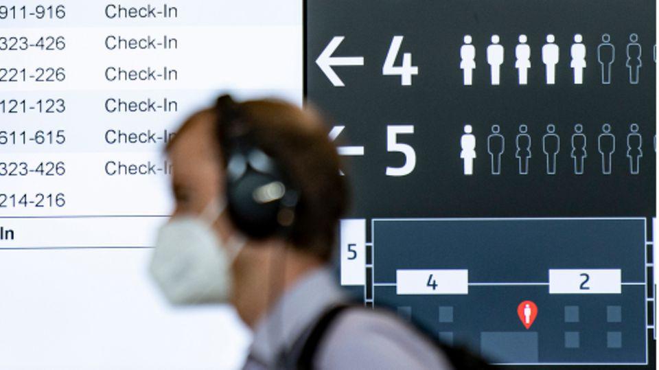 Ein Mann mit Maske geht an einer Anzeigetafel am Flughafen BER vorbei