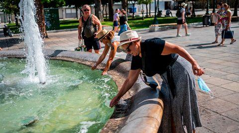 Touristen erfrischen sich bei Temperaturen über 40 Grad mit Wasser aus einem Brunnen auf dem Syntagma-Platz in Athen