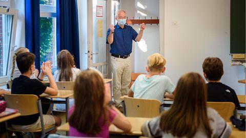 Ein Schulleiter begrüßt im vergangenen Herbst seine Schüler am ersten Schultag