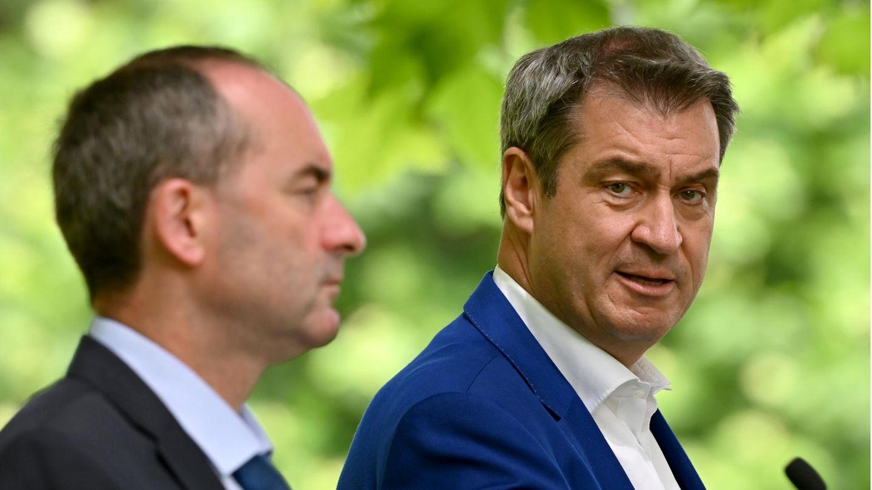 Zwei mittelalte weiße Männer stehen in Anzügen im freien. Der im Hintergrund dreht seinen Kopf zu dem im Vordergrund