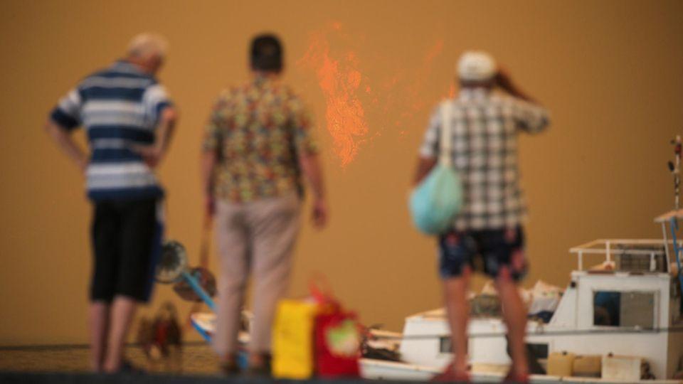 Türkei, Bodrum: Touristen stehen während eines Waldbrands auf einem Steg und warten darauf, evakuiert zu werden