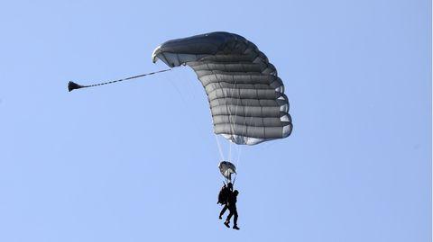 Vor einem wolkenlosen Himmel sind die Konturen zweier Personen zu sehen, die an einem grauen Fallschirm hängen