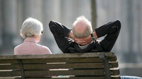 Von hinten sind eine weißhaarige Frau und ein weißhaariger Mann mit Halbglatze zu sehen, die auf einer Bank in der Sonne sitzen