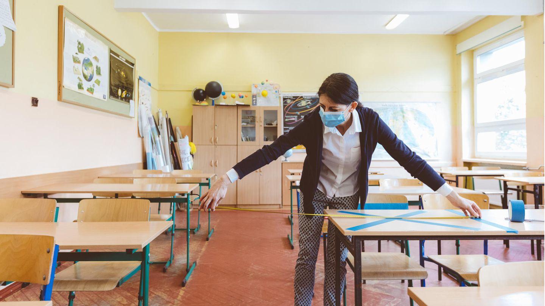 Eine Lehrerin misst den Abstand zwischen den Arbeitsplätzen der Schüler:innen