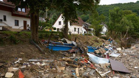 Trümmer liegen an einer Böschung unterhalb einer Wohnstraße, an der zwei weißt Einfamilienhäuser stehen