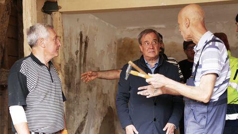 Laschet steht im Swisttaler Ortsteil Odendorf mit Anwohnern in einem zerstörten Haus