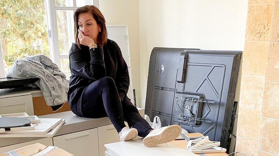 Danni Büchner sitzt in ihrem neuen Wohnzimmer zwischen Kisten.